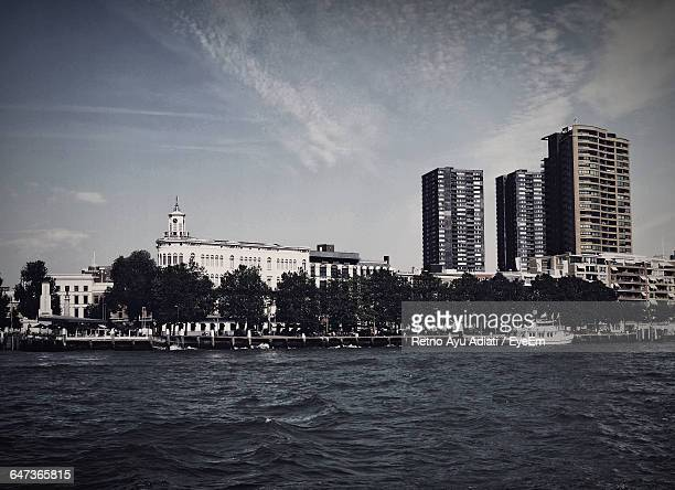 Low Angle View Of Buildings In Front Of River Against Cloudy Sky In City