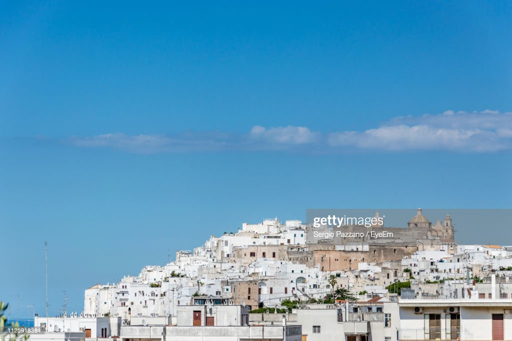 Low Angle View Of Buildings In Town Against Blue Sky : Stock Photo