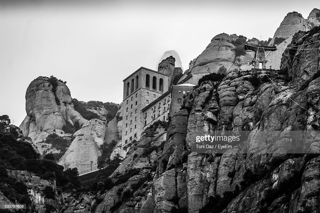 Low Angle View Of Buildings On Rocky Mountains Against Sky : Foto stock