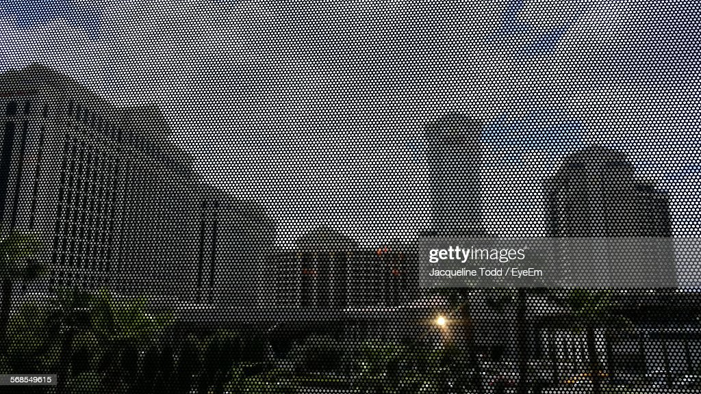 Low Angle View Of Buildings Seen Through Metal Grate : Stock Photo