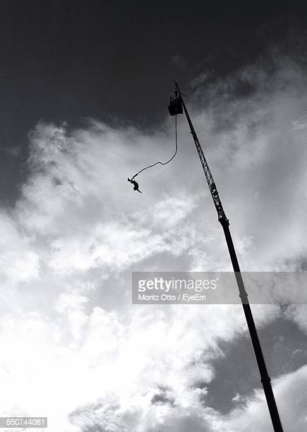 Low Angle View Of Bungee Jumping Against Cloudy Sky