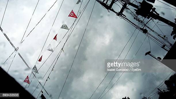 Low Angle View Of Bunting And Cables Against Cloudy Sky
