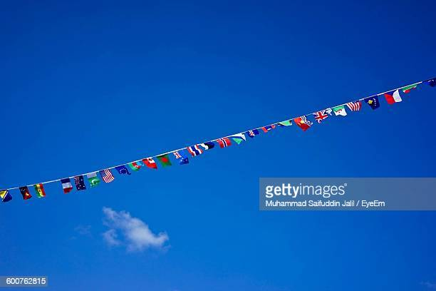 Low Angle View Of Bunting Flags Against Blue Sky