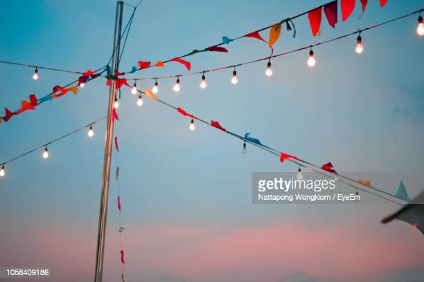 low angle view of bunting flags and light bulbs hanging against sky during sunset - hanging stock pictures, royalty-free photos & images