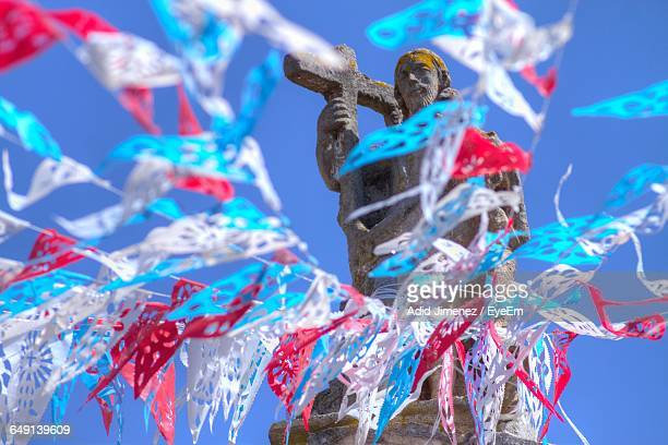 Low Angle View Of Bunting Flags By Jesus Christ Statue Against Sky