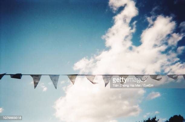 low angle view of buntings hanging against blue sky - banderines fotografías e imágenes de stock