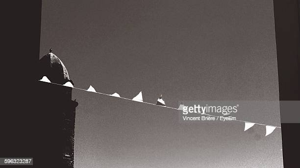 low angle view of buntings hanging amidst buildings against sky at collioure - collioure photos et images de collection