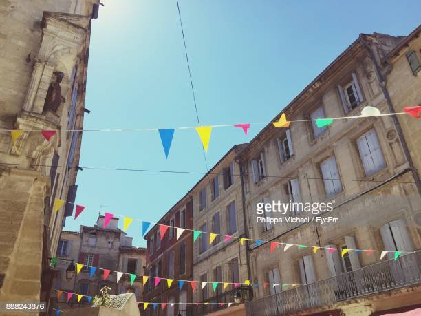 low angle view of buntings hanging amidst buildings against sky - banderines fotografías e imágenes de stock