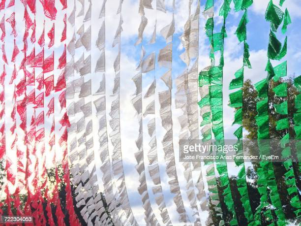 Low Angle View Of Buntings Imitating Mexican Flag Against Sky