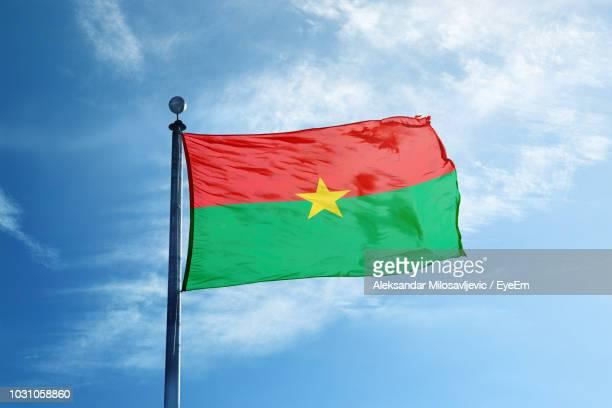 low angle view of burkina faso flag against blue sky - ブルキナファソ ストックフォトと画像