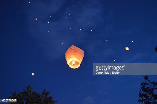 low angle view of burning sky lanterns against sky at night - lantern stock photos and pictures