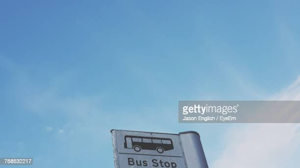 Low Angle View Of Bus Stop Sign Against Blue Sky