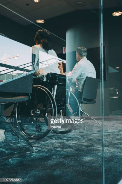 low angle view of business people sitting in board room during meeting seen through glass - persons with disabilities stock pictures, royalty-free photos & images
