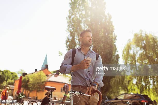 Low angle view of businessman holding bicycle and smart phone on sunny day