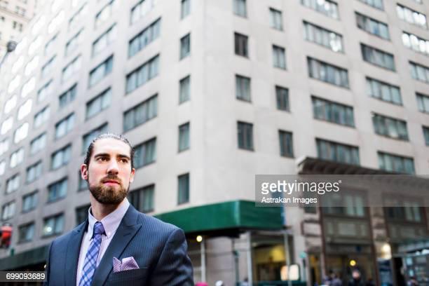 low angle view of businessman standing against buildings in city - pochette bavero foto e immagini stock