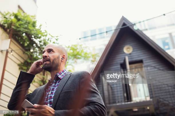 Low angle view of businessman talking through in-ear headphones at office yard
