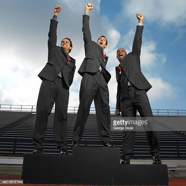 low angle view of businessmen standing in a stadium wearing  medals raising their hands in victory