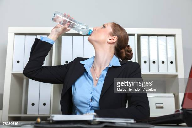 Low Angle View Of Businesswoman Drinking Water At Office