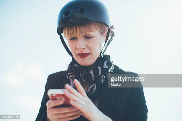 Low angle view of businesswoman in cycling helmet using mobile phone against sky