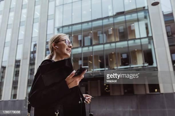 low angle view of businesswoman talking through in-ear headphones in city - financiën en economie stockfoto's en -beelden