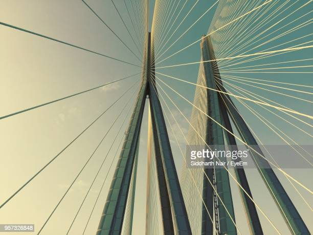 low angle view of cables against sky - suspension bridge stock photos and pictures