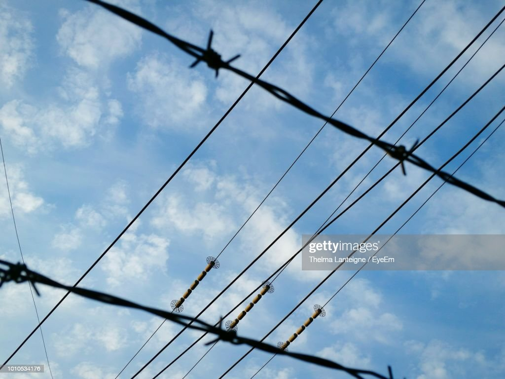 Low Angle View Of Cables And Barbed Wire Fence Against Sky Stock ...