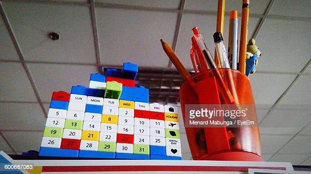 Low Angle View Of Calendar By School Supplies In Container