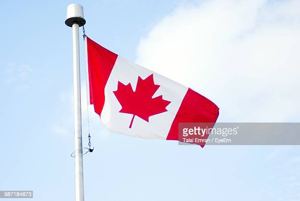 Low Angle View Of Canadian Flag Against Cloudy Sky