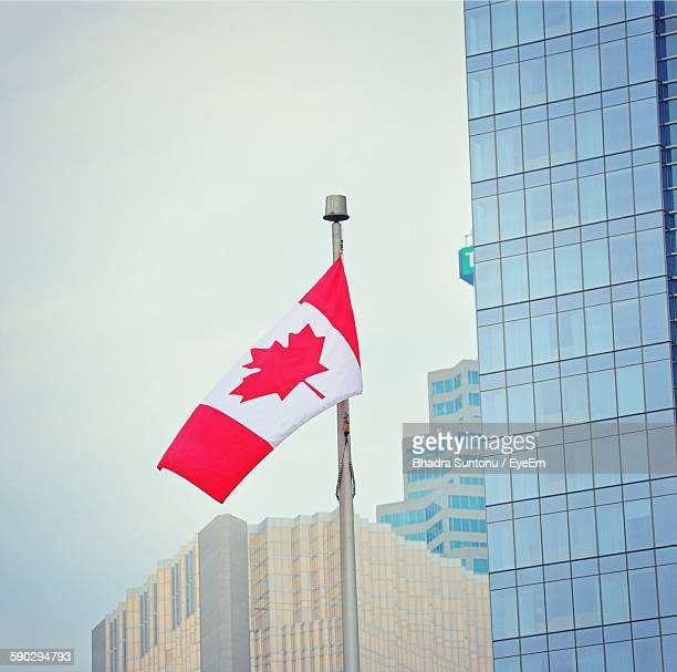 Low Angle View Of Canadian Flag And Buildings Against Clear Sky