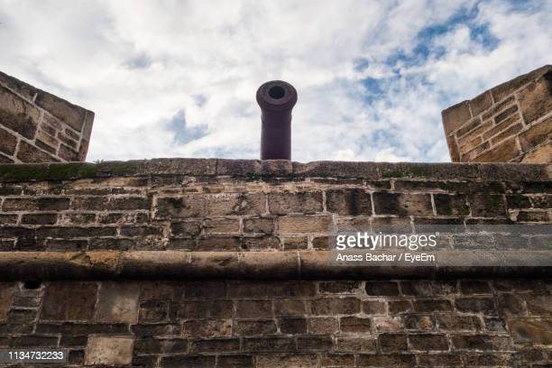 Low Angle View Of Cannon On Brick Wall Against Cloudy Sky
