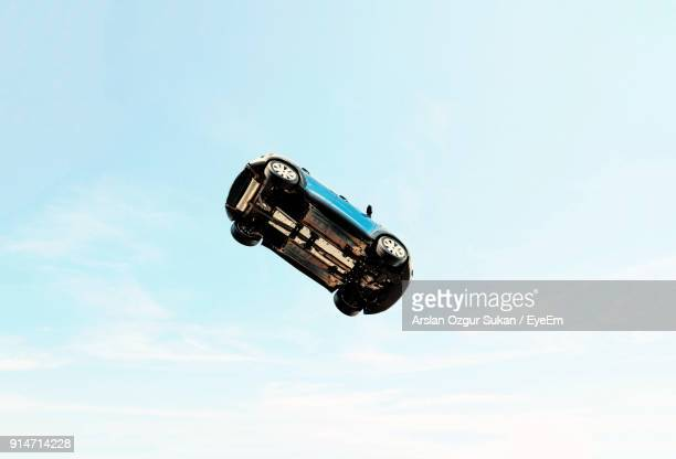 low angle view of car jumping against blue sky - in de lucht zwevend stockfoto's en -beelden