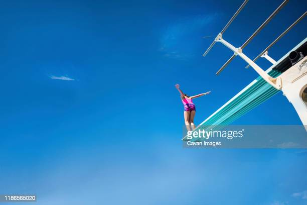 low angle view of carefree girl standing on diving platform against blue sky during sunny day - diving board stock pictures, royalty-free photos & images