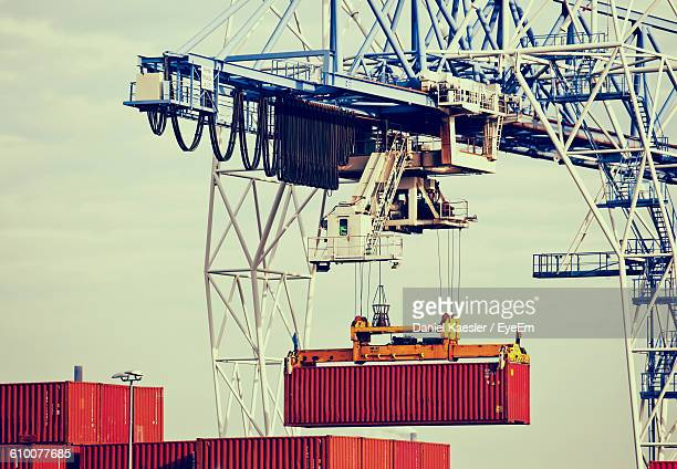 Low Angle View Of Cargo Containers And Crane At Harbor