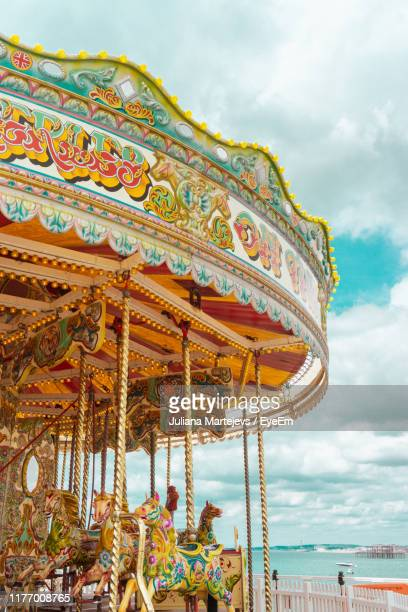 low angle view of carousel against cloudy sky - brighton stock pictures, royalty-free photos & images