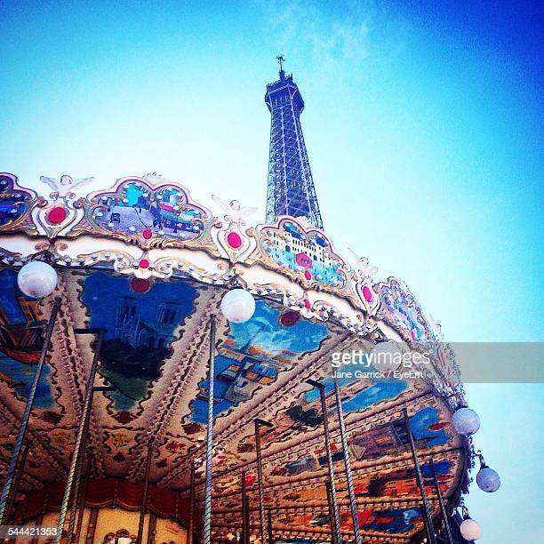 Low Angle View Of Carousel And Eiffel Tower Against Blue Sky