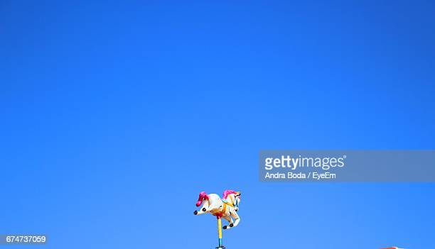 Low Angle View Of Carousel Horse Against Clear Blue Sky
