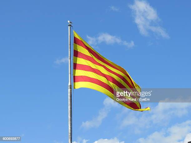Low Angle View Of Catalan Flag Waving Against Sky