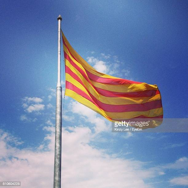 Low angle view of Catalonia flag fluttering against blue sky and clouds