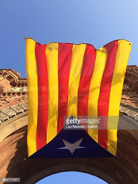 Low Angle View Of Catalonia Flag Hanging On Arc De Triomf Against Sky