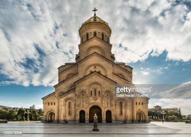 low angle view of cathedral against cloudy sky - tbilisi stockfoto's en -beelden