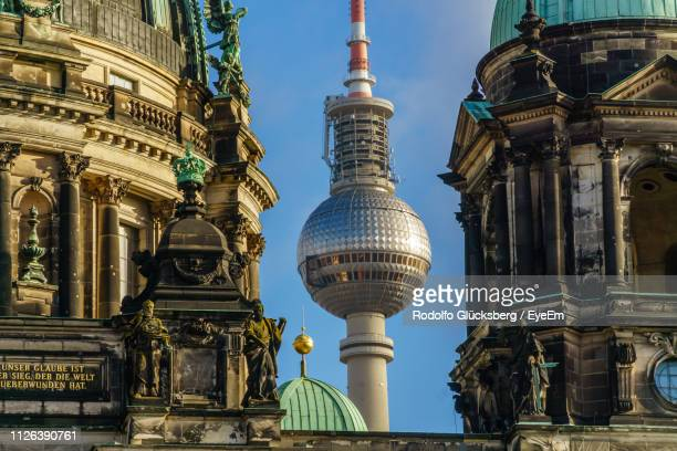 low angle view of cathedral and fernsehturm against sky - television tower berlin stock pictures, royalty-free photos & images