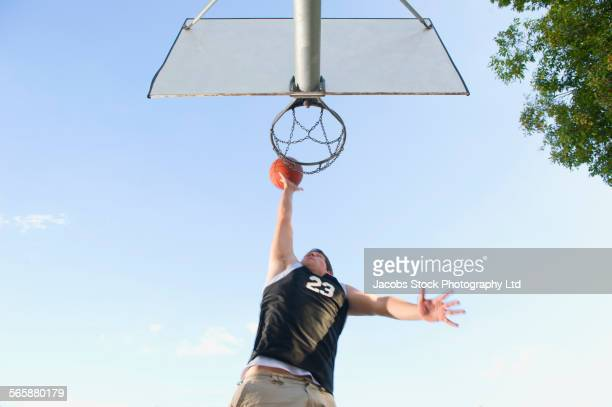 Low angle view of Caucasian basketball player dunking in hoop