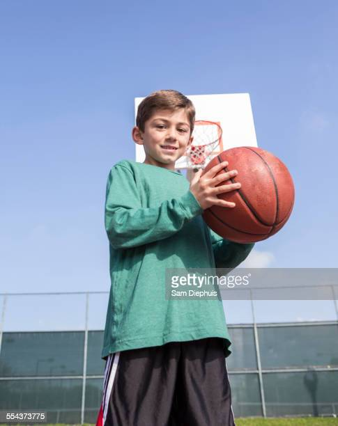 Low angle view of Caucasian boy holding basketball on court