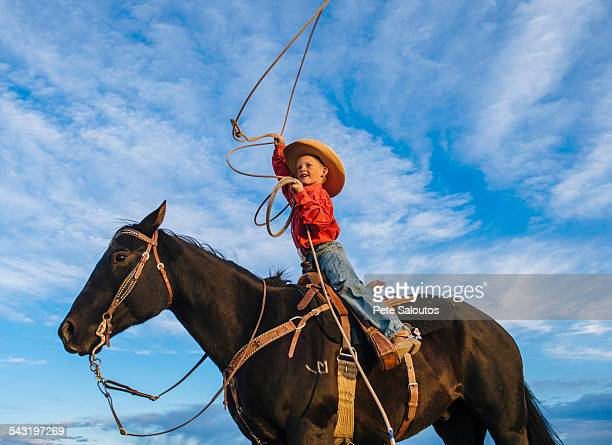 Low angle view of Caucasian boy on horse throwing lasso