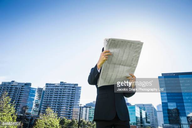 Low angle view of Caucasian businessman reading newspaper outdoors