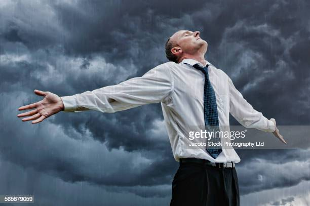 Low angle view of Caucasian businessman standing in rainstorm