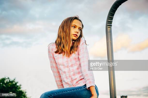 Low angle view of Caucasian girl sitting outdoors