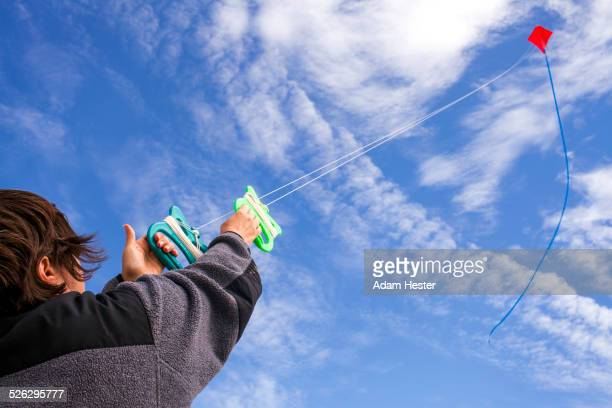 Low angle view of Caucasian man flying kite in blue sky
