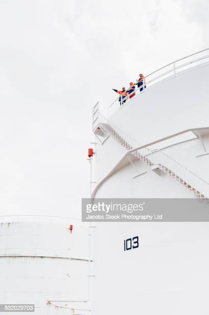 low angle view of caucasian technicians standing on fuel storage tank - storage tank stock pictures, royalty-free photos & images