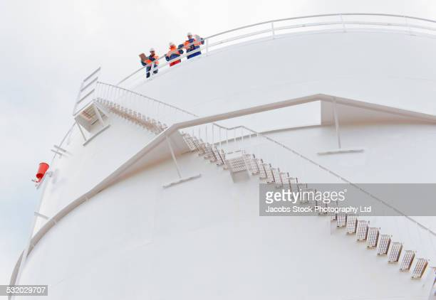 Low angle view of Caucasian technicians standing on fuel storage tank